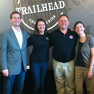 Photo of Cameron, Kim, Jim and Ula standing in front of the Trailhead logo.