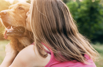 Woman kissing golden retriever