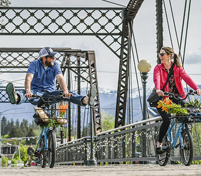 couple riding bicycles on a bridge