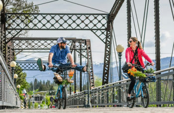 Two people biking over a bridge