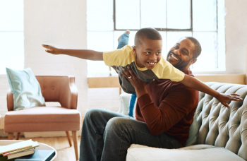 Father playing airplane with son
