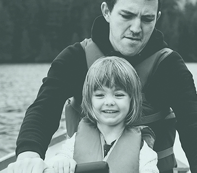 Father and daughter rowing a boat on a lake